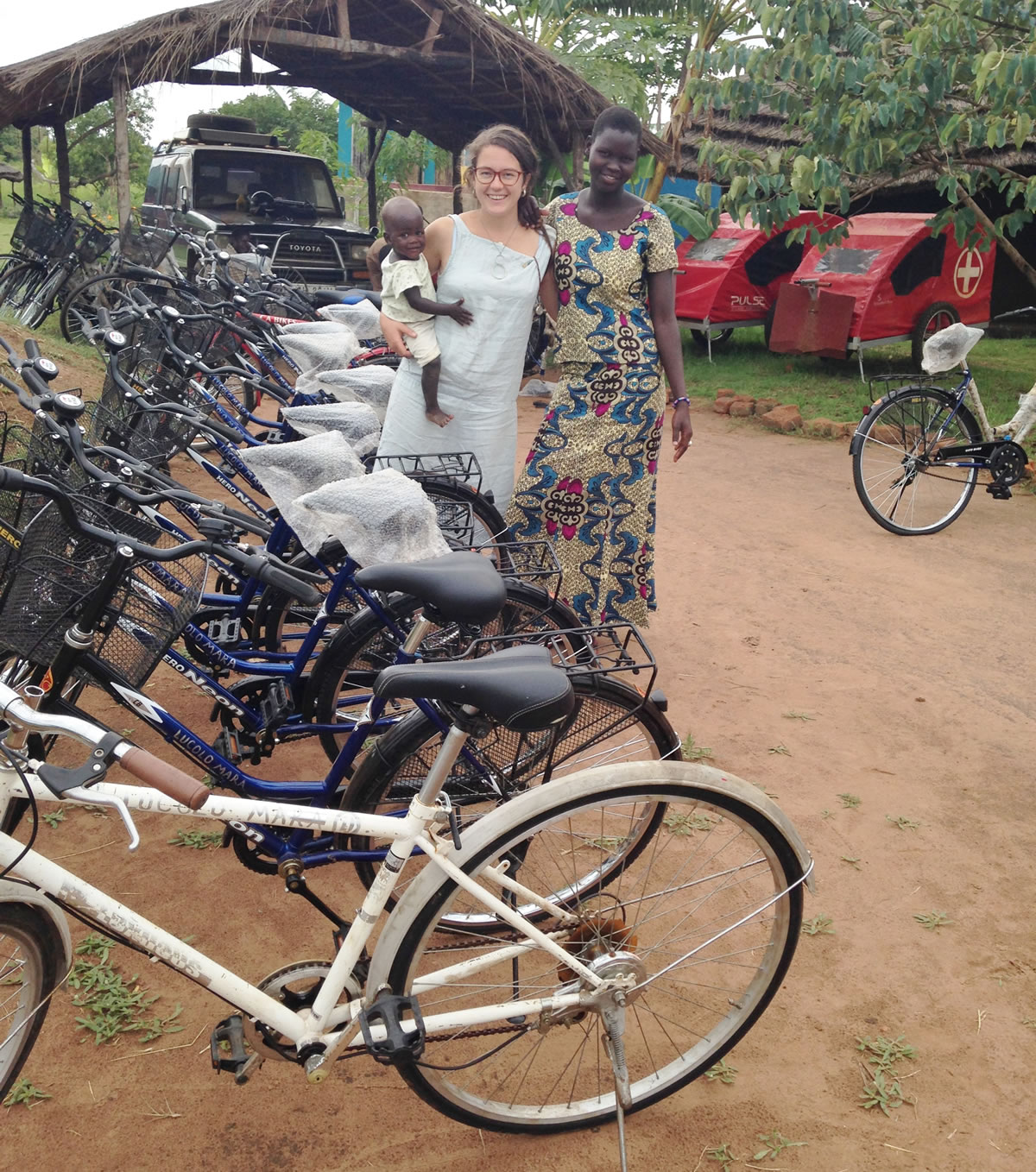 Emily Hill from Mobilise a Midwife with Ugandan woman and baby next to donated bikes