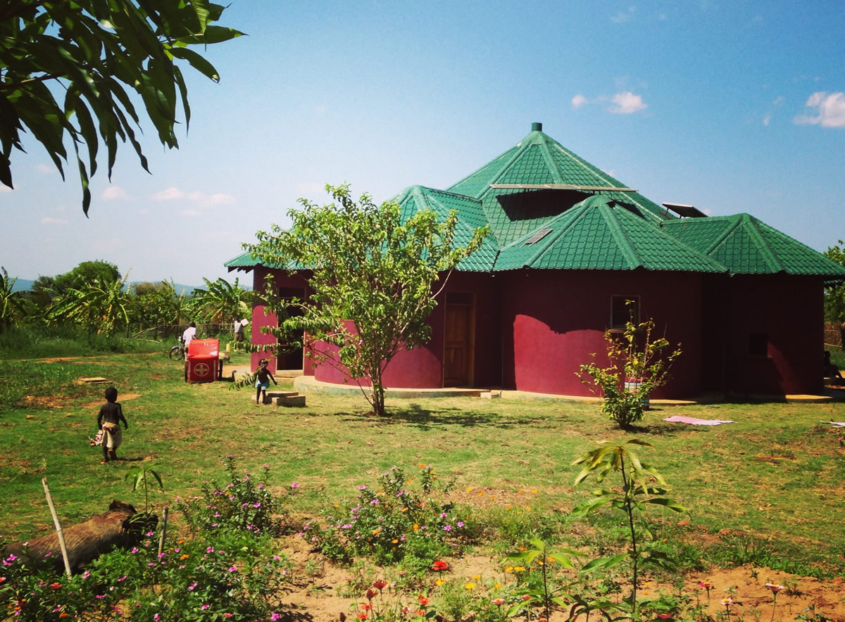 Aid house in Uganda with trees and children playing