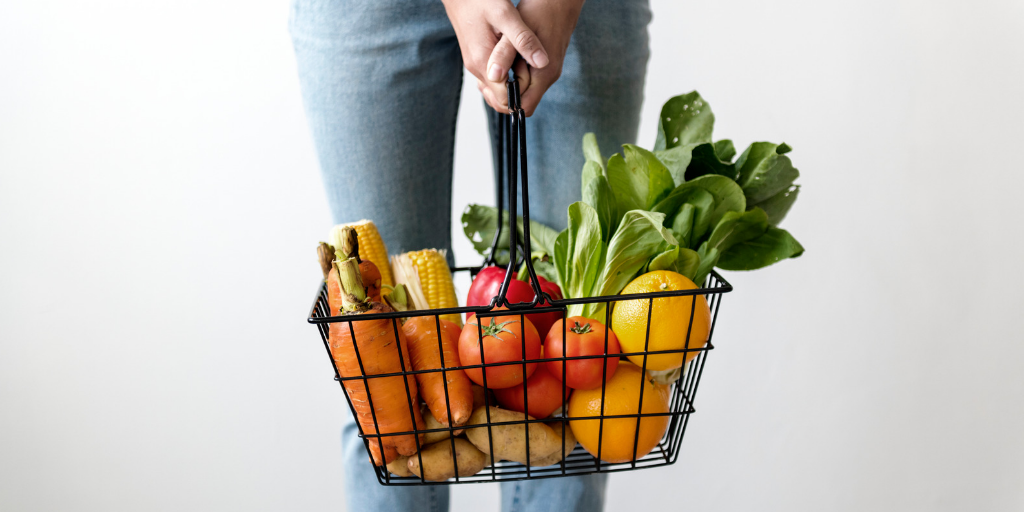 person holding a basket of fresh fruit and vegetables